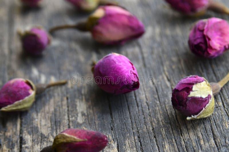 Seque las flores color de rosa de los brotes en la tabla de madera vieja Ingrediente asiático para la infusión de hierbas del aro fotografía de archivo