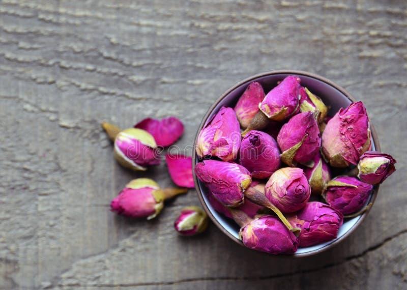 Seque las flores color de rosa de los brotes en un cuenco en la tabla de madera vieja Concepto herbario sano de las bebidas Ingre imagenes de archivo