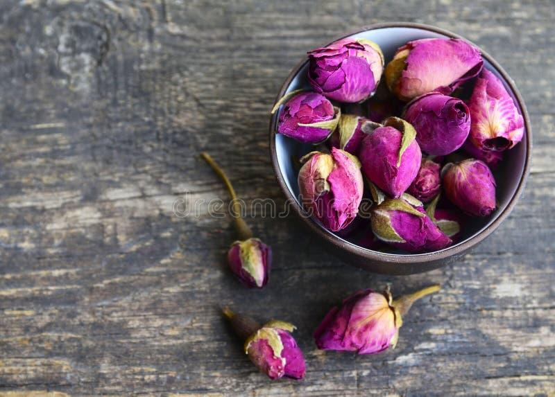 Seque las flores color de rosa de los brotes en un cuenco en la tabla de madera vieja Concepto herbario sano de las bebidas Ingre fotografía de archivo