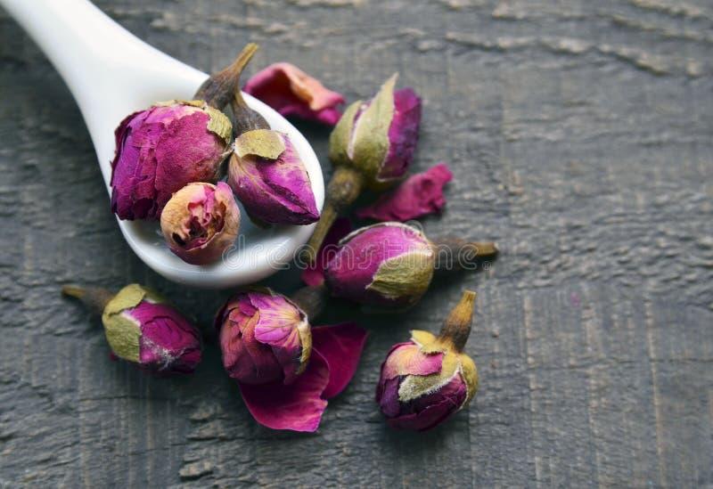 Seque las flores color de rosa de los brotes en una cuchara blanca en la tabla de madera vieja Ingrediente asiático para la infus foto de archivo