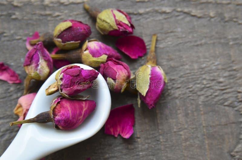 Seque las flores color de rosa de los brotes en una cuchara blanca en la tabla de madera vieja Ingrediente asiático para la infus imágenes de archivo libres de regalías
