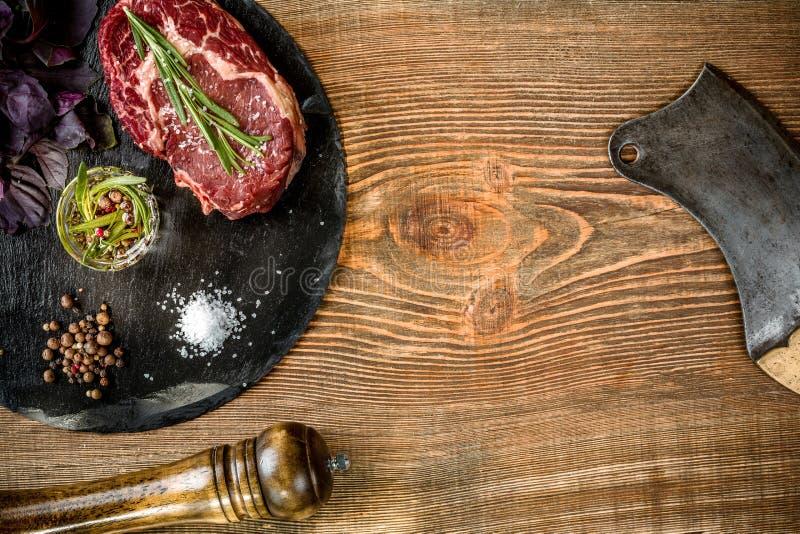 Seque o bife cru envelhecido com os ingredientes para grelhar fotografia de stock