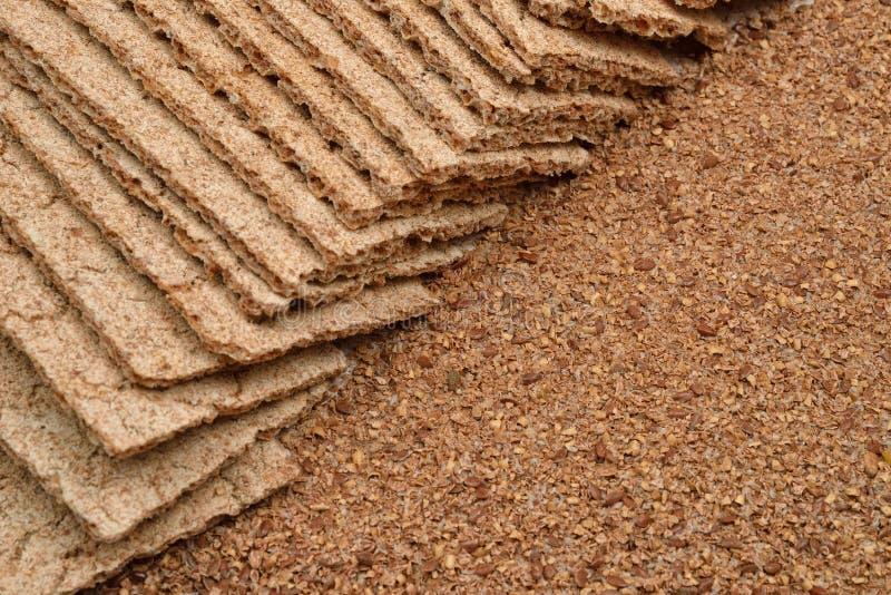 Seque pães torrados da dieta e a farinha de trigo integral no backgro de madeira imagens de stock royalty free