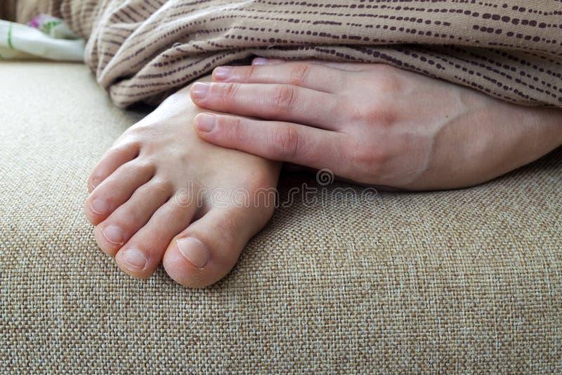 Seque pele rachada dos pés da mulher na cama Tratamento do pé imagem de stock royalty free