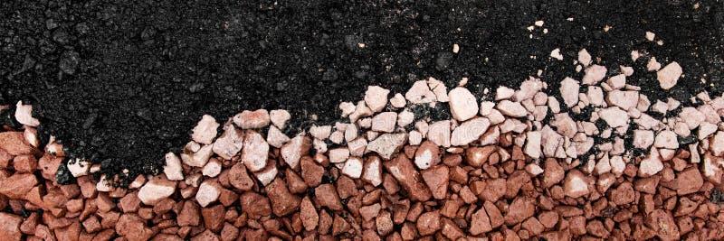 Sequedad caliente del asfalto en curso bajo con grava y piedras foto de archivo libre de regalías