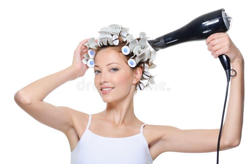 Sequedad de la mujer su cabeza en pelo-bigudíes imágenes de archivo libres de regalías