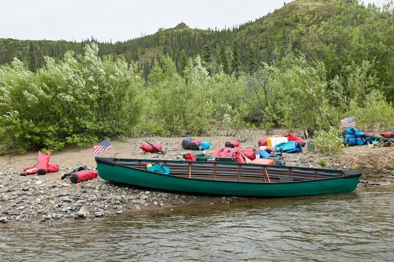 Sequedad varada de la canoa y del engranaje en riverbank fotos de archivo