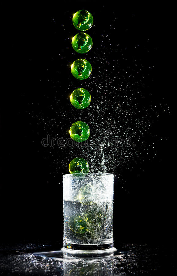 Ball sequence falling into a water glash royalty free stock photos