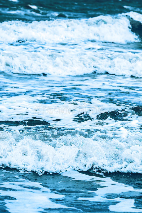 Sequence of waves beating against shore. Number of surging waves in tide without people. Abstract background stock photo