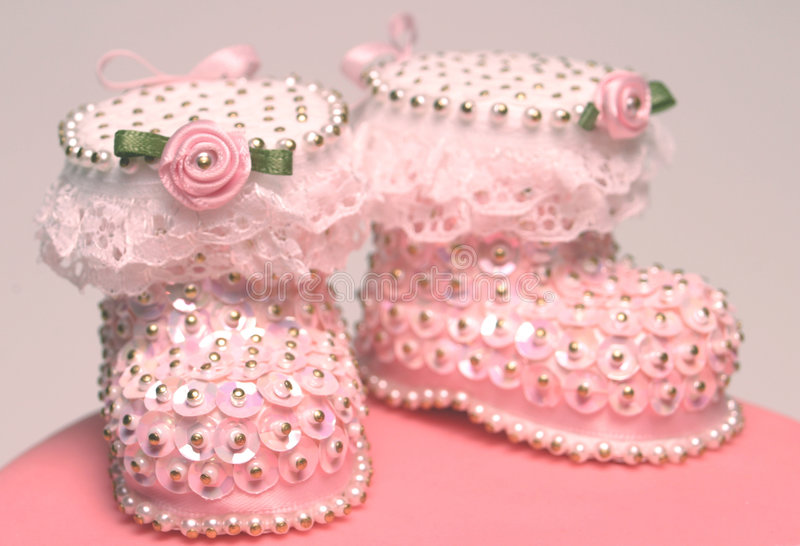 Sequin Bootees. Pair of sequin bootees on christening cake royalty free stock photo