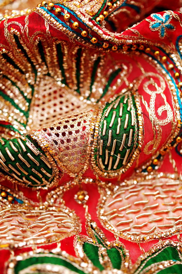 Sequin embroidery. Golden red sequin embroidery with silky fabric royalty free stock photo