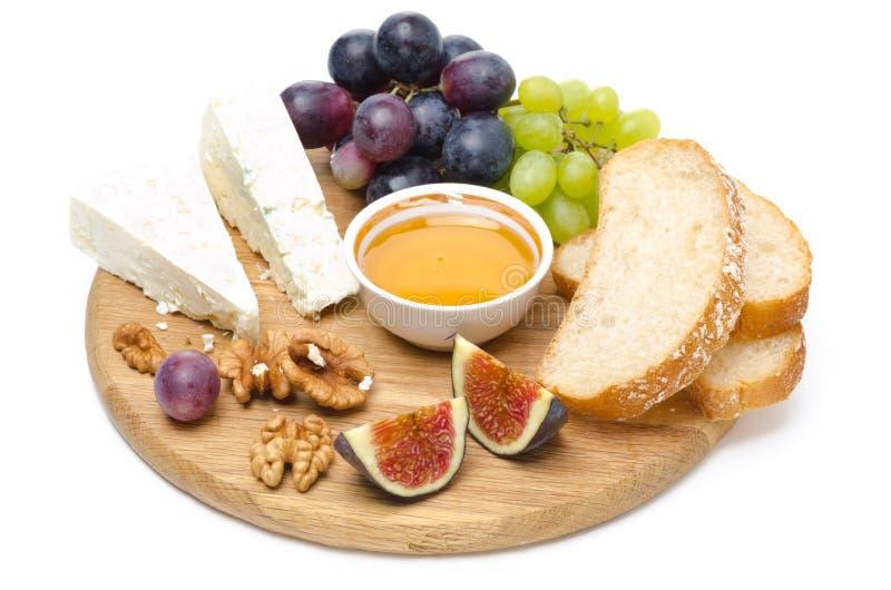 Ser, chleb, figi, winogrona, miód i dokrętki na drewnianej desce, fotografia royalty free
