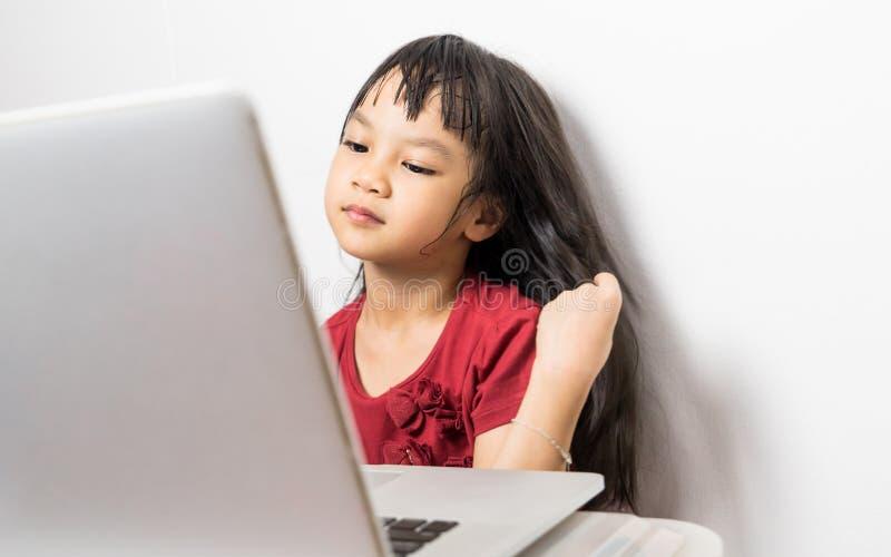 Ser den asiatiska flickan för långt hår härlig genom att använda den videopd appellen på internet royaltyfria bilder