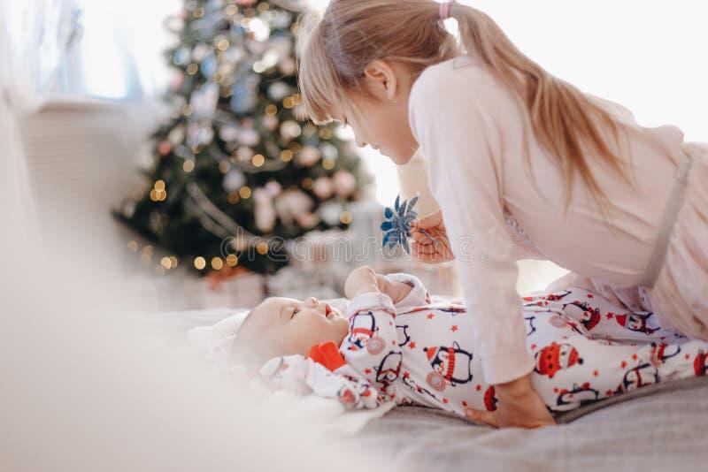 Ser den iklädda pajamaen för lilla flickan hennes mycket lilla broder som ligger på sängen i det hemtrevliga rummet med det n royaltyfria foton