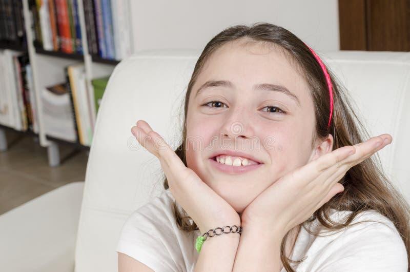 Ser den tonårs- brunetten för flicka kameran med leende royaltyfri bild