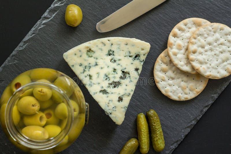 Ser deska z błękitnej foremki serem, oliwkami, zalewami i krakers, zdjęcie royalty free
