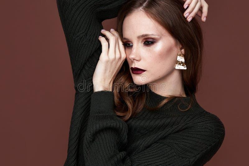 Ser härliga sexiga brunettkvinnor för glamour, som en modell som bär afton, utgör i mager stucken klänning i mode poserar perfekt arkivfoto