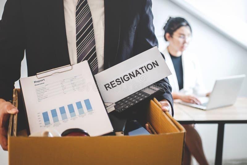 Ser preparado homem de negócios da vontade que envia a carta de demissão à empresa e que leva pertences e arquivos da embalagem n foto de stock