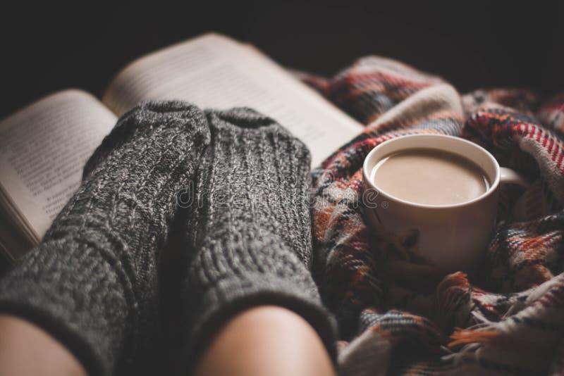 Sera accogliente con una tazza di caffè caldo e di un libro fotografia stock