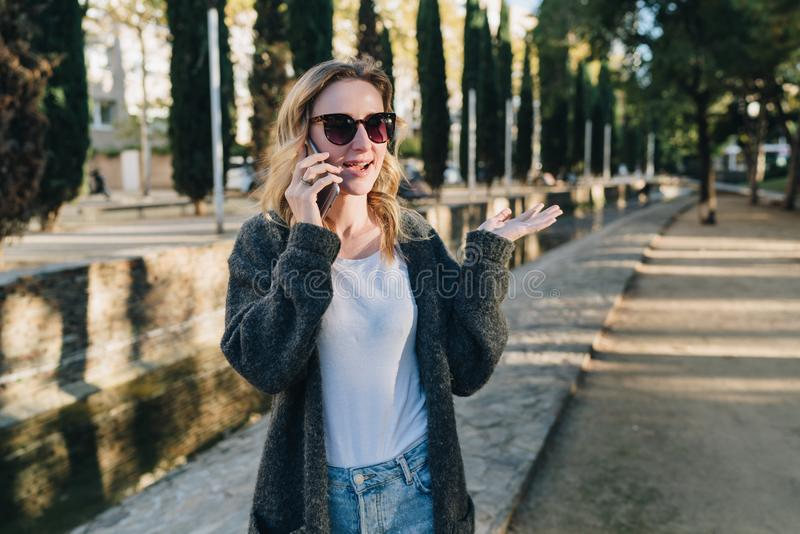 Sera di estate Una giovane donna attraente in occhiali da sole sta felicemente nel parco e nei colloqui sul suo telefono cellular fotografia stock