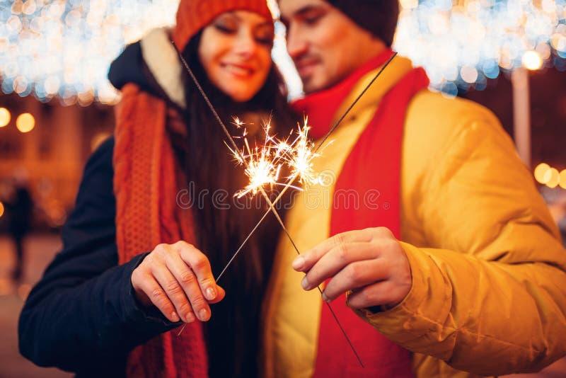 Sera di inverno, coppia di amore con le stelle filante all'aperto immagini stock libere da diritti