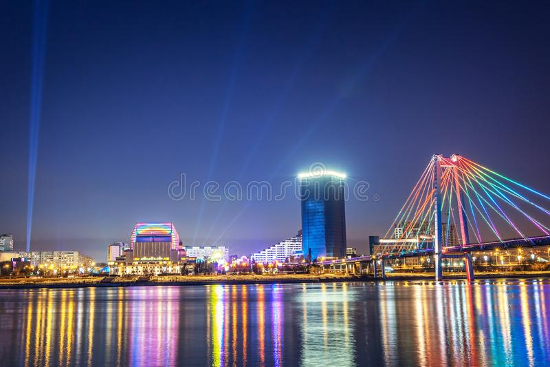 Sera e notte Krasnojarsk, città di notte di panorama Ponte strallato nelle luci intense Paesaggio urbano fotografie stock libere da diritti