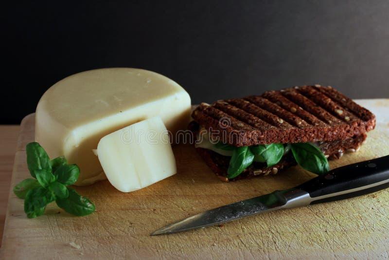 Sera i basila grzanka na drewnianej tnącej desce z ostrze fantazji nożem gotowym jedzącym zdjęcie royalty free