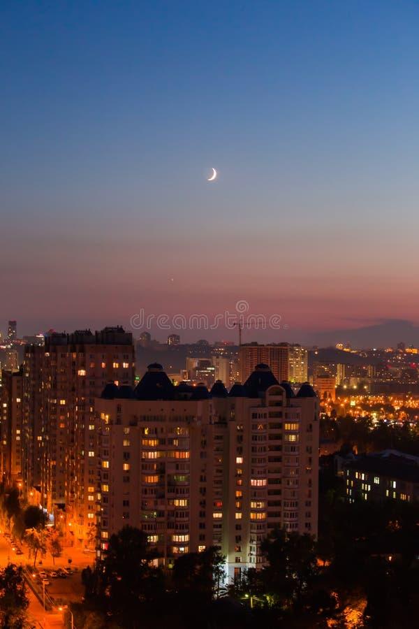 Sera a Kiev, una città di vista superiore, le vie di notte e la nuova luna nel cielo fotografia stock libera da diritti