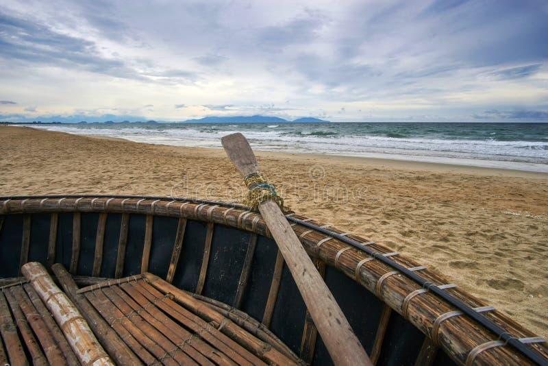 Sera tempestosa alla spiaggia con le nuvole e le onde drammatiche Crogiolo vietnamita tradizionale di noce di cocco nella priorit fotografia stock libera da diritti