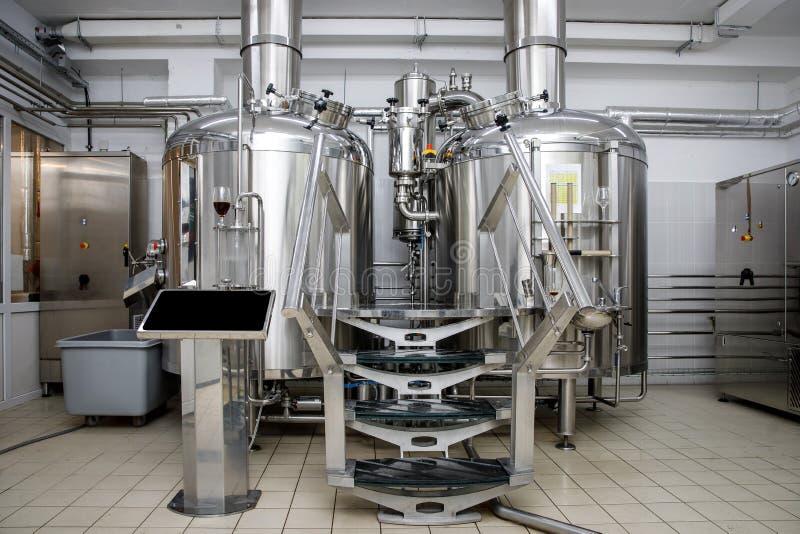 Serbatoi di acciaio di produzione della fabbrica di birra e tubi moderni, birra del mestiere nel microbirrificio immagini stock libere da diritti