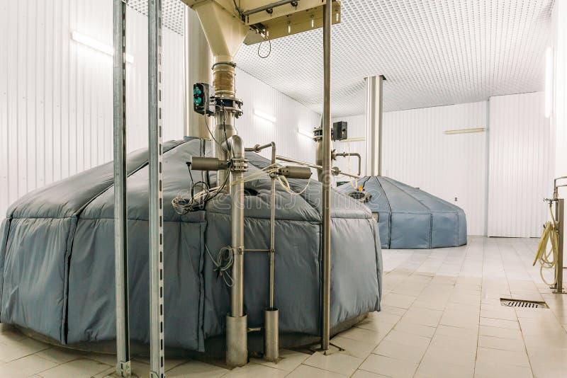 Serbatoi di acciaio di stoccaggio o cisterne e tubi per fermentazione della birra nella fabbrica industriale di produzione della  immagine stock