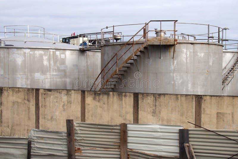 Serbatoi industriali del vecchio metallo con le scale arrugginite di ispezione e valvole circondate da un recinto e da una parete fotografia stock libera da diritti