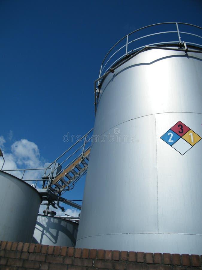Serbatoi industriali per i prodotti chimici con la segnaletica di sicurezza immagini stock