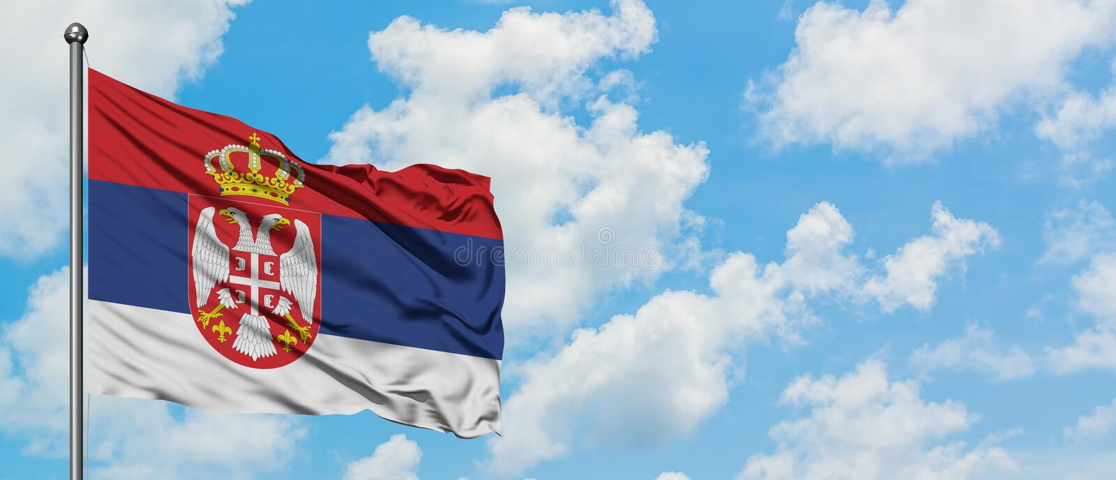 Serbia flag waving in the wind against white cloudy blue sky. Diplomacy concept, international relations.  royalty free stock images
