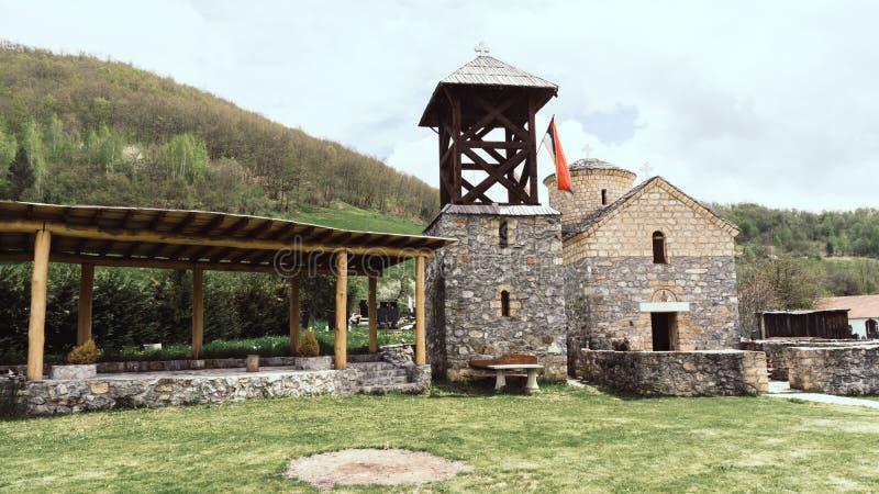 Serbische Flagge der orthodoxen Kirche durch einen kleinen Schrein Sakrale Architektur orthodoxe Kirche crkva svetog jovan krstit stockbild