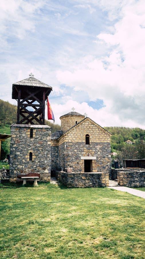 Serbische Flagge der orthodoxen Kirche durch einen kleinen Schrein Sakrale Architektur orthodoxe Kirche crkva svetog jovan krstit lizenzfreie stockfotografie