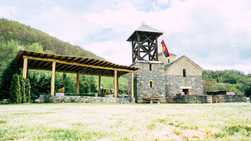 Serbische Flagge der orthodoxen Kirche durch einen kleinen Schrein Sakrale Architektur orthodoxe Kirche crkva svetog jovan krstit lizenzfreies stockbild