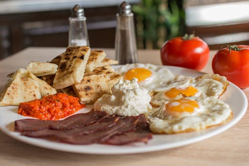 Serbisk frukost med för ost, ajvar och hemlagad bröd för ägg, för skinka, royaltyfria bilder