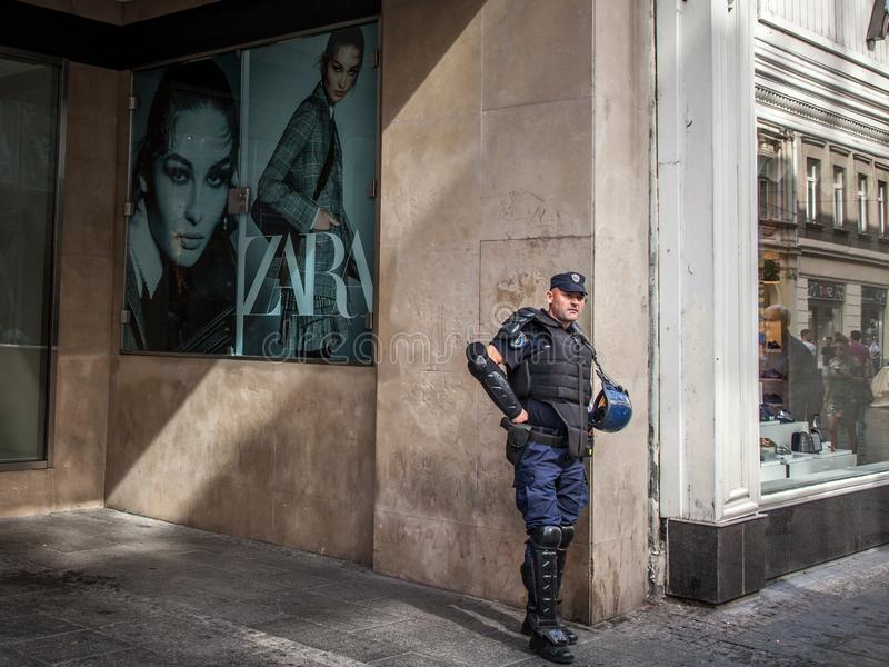 Serbisk polis som framme står av ett modelager med anti-tumultkugghjulet i mitten av Belgrade, Serbien, under Gay Pride royaltyfri fotografi