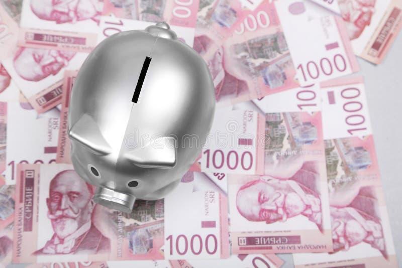 Serbiska dinarkassapengar och silverspargris på tabellen royaltyfri bild