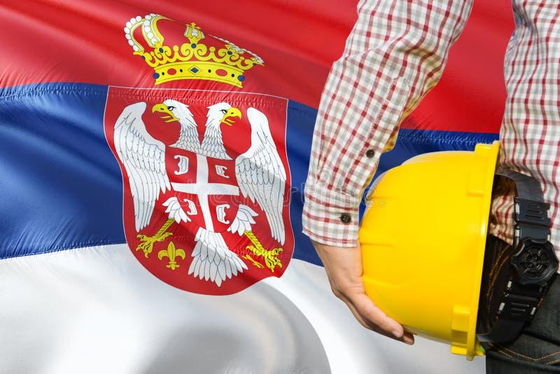 Serbski inżynier trzyma żółtego zbawczego hełm z machać Serbia chorągwianego tło Budowy i budynku poj?cie zdjęcia royalty free