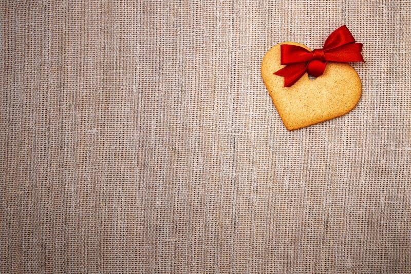 Serca kształtny piernikowy ciastko z czerwonym faborkiem zdjęcia stock