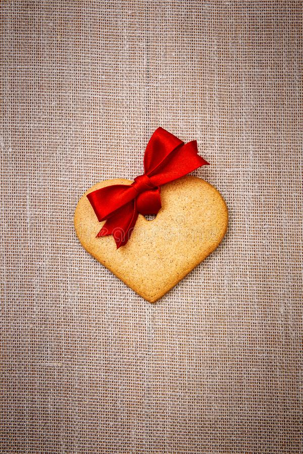 Serca kształtny piernikowy ciastko z czerwonym faborkiem fotografia royalty free