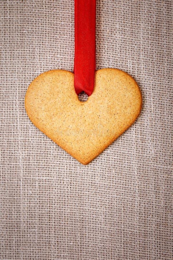 Serca kształtny piernikowy ciastko z czerwonym faborkiem zdjęcia royalty free