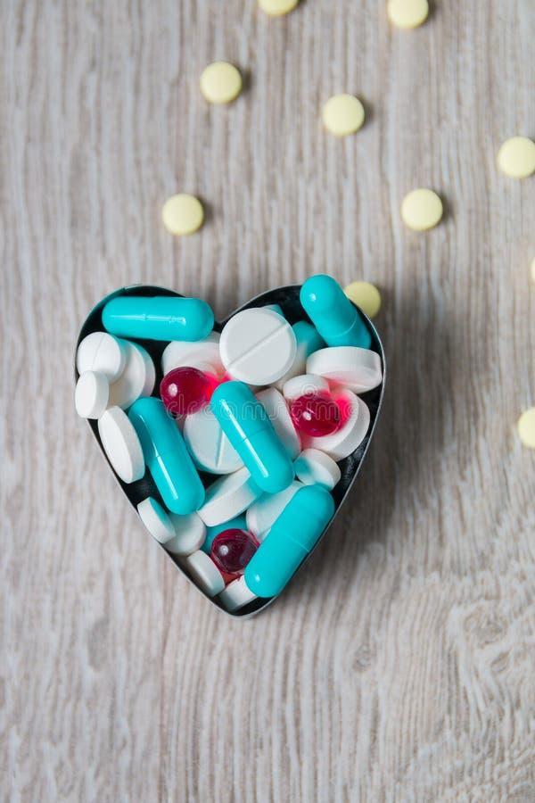 Serce above od kolorowego lekarstwa i pigułki na popielatym drewnianym tle kosmos kopii Odgórny widok, rama Środki przeciwbólowi, obrazy stock