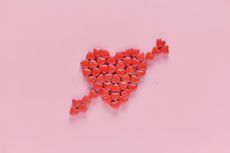 Serce był hafciarski strzałkowatym kształtem medycyn pigułki na różowym tle obrazy stock