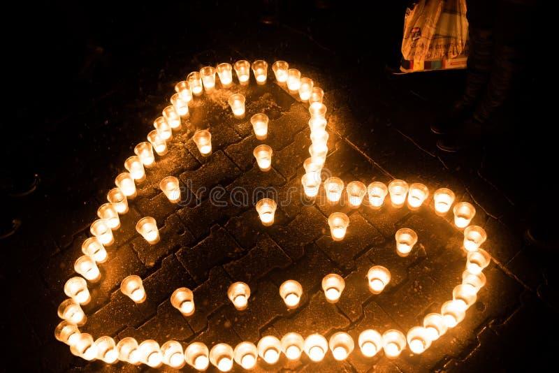 Serce komponował świeczki, na ziemi, przy nocą fotografia stock