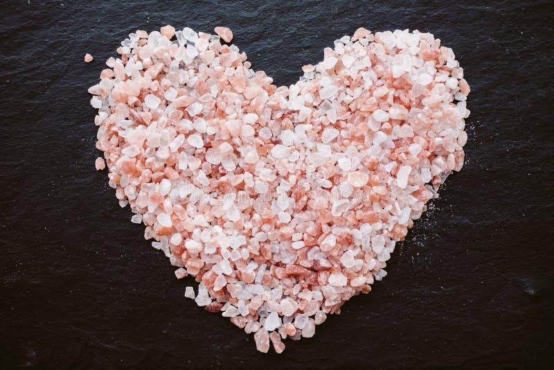 Serce kształtna Himalajska sól na pokładzie tła Odgórny widok zdjęcie stock