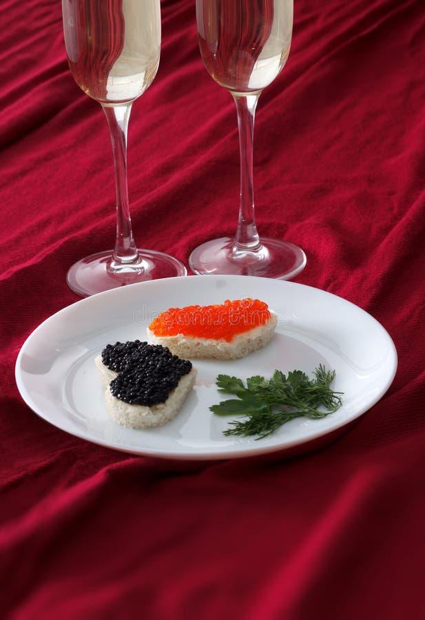 Serce kształtował grzanki z kawiorem i dwa szkłami szampan na bielu talerzu na czerwonej draperii czerwonym i czarnym zdjęcie royalty free