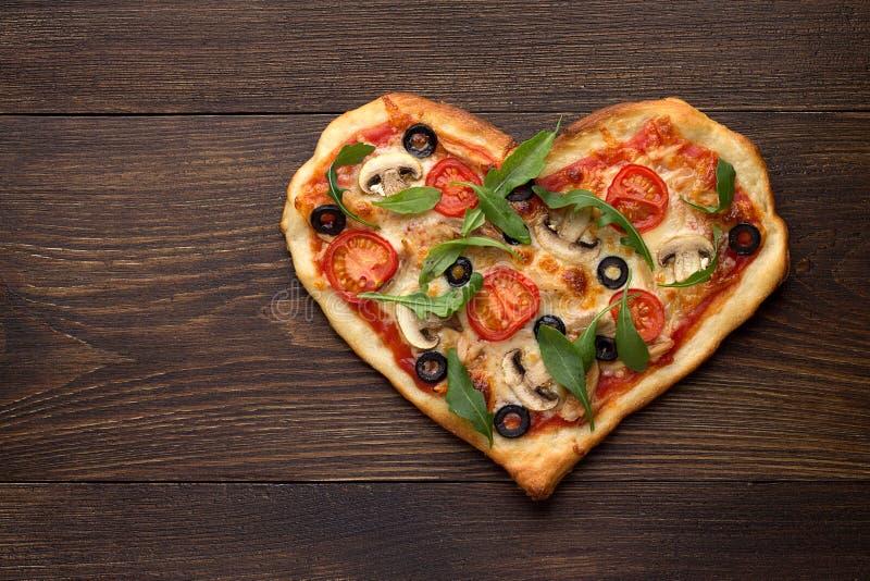 Serce kształtował pizzę z kurczakiem i pieczarkami na ciemnym drewnianym rocznika tle zdjęcie royalty free